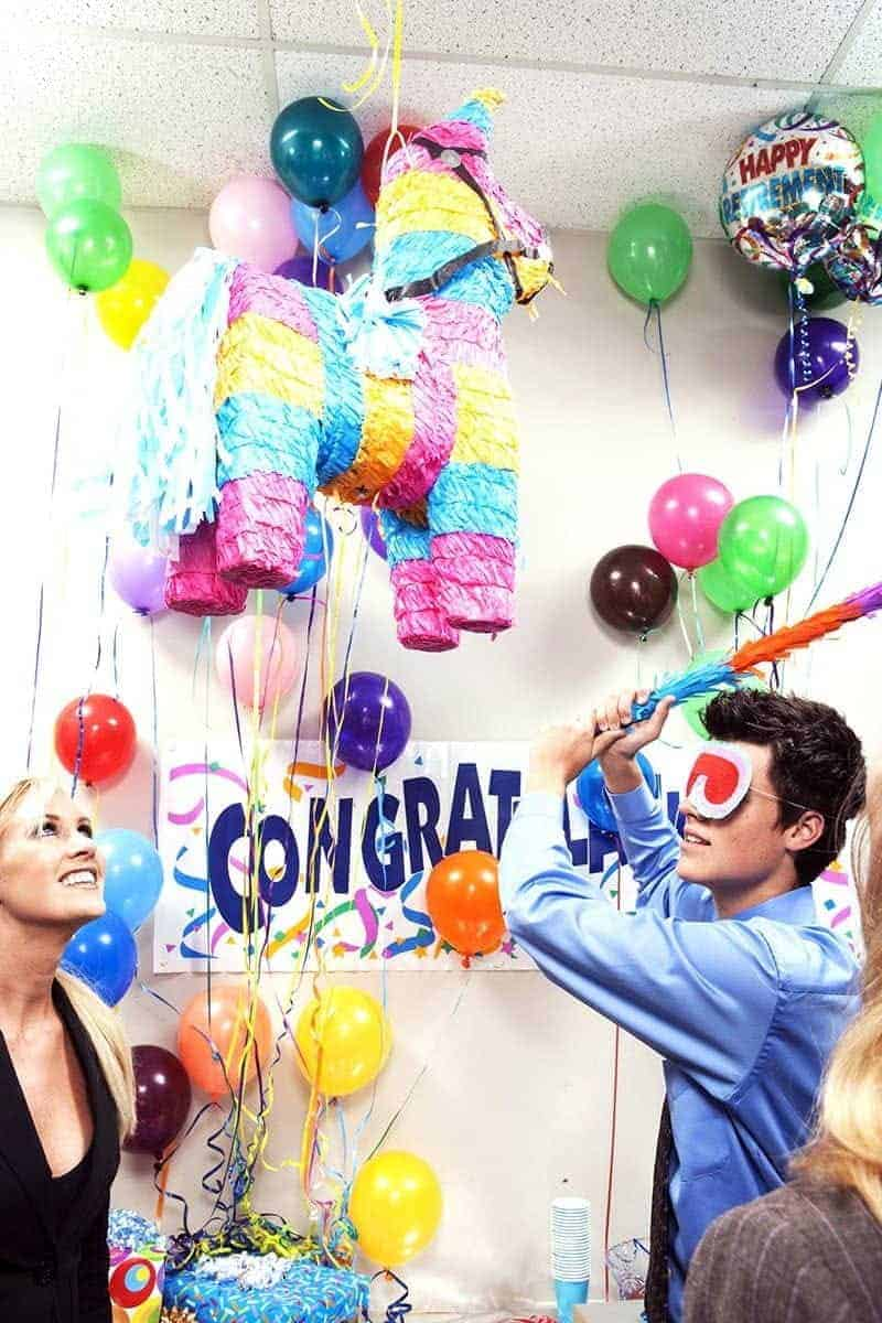 man swinging at a pinata with party supplies and party city coupons