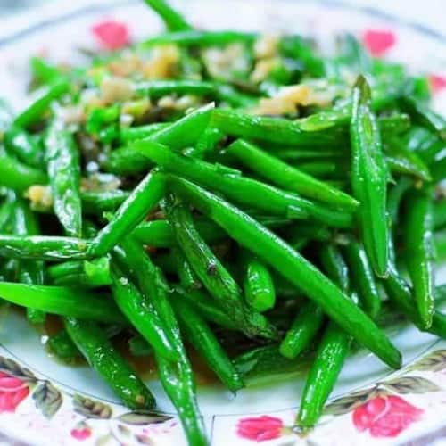 garlic green beans on a white bowl with pink flowers