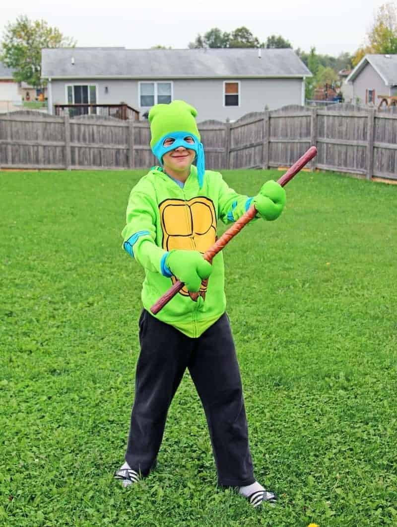 boy wearing a Ninja Turtle Costume in the grass