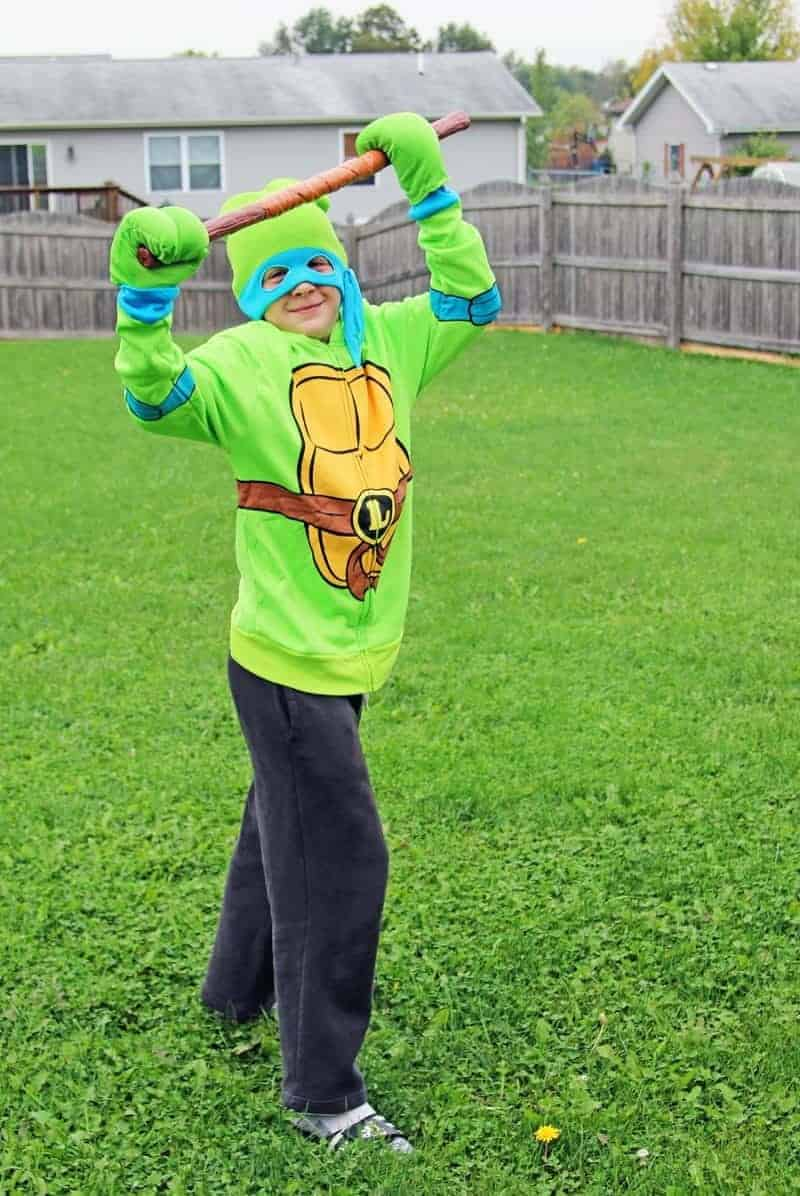 boy wearing a ninja turtle costume outside in the grass