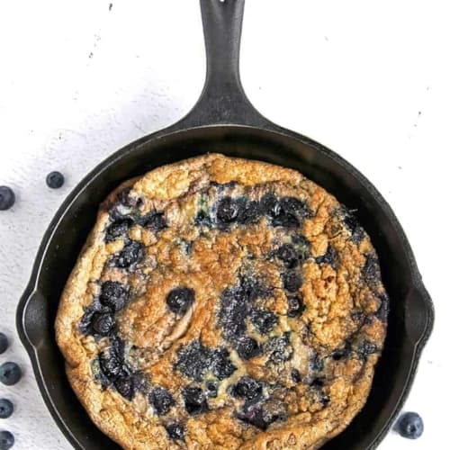 Low Carb Egg strate with Blueberries and Cinnamon in a cast iron pan on a white background