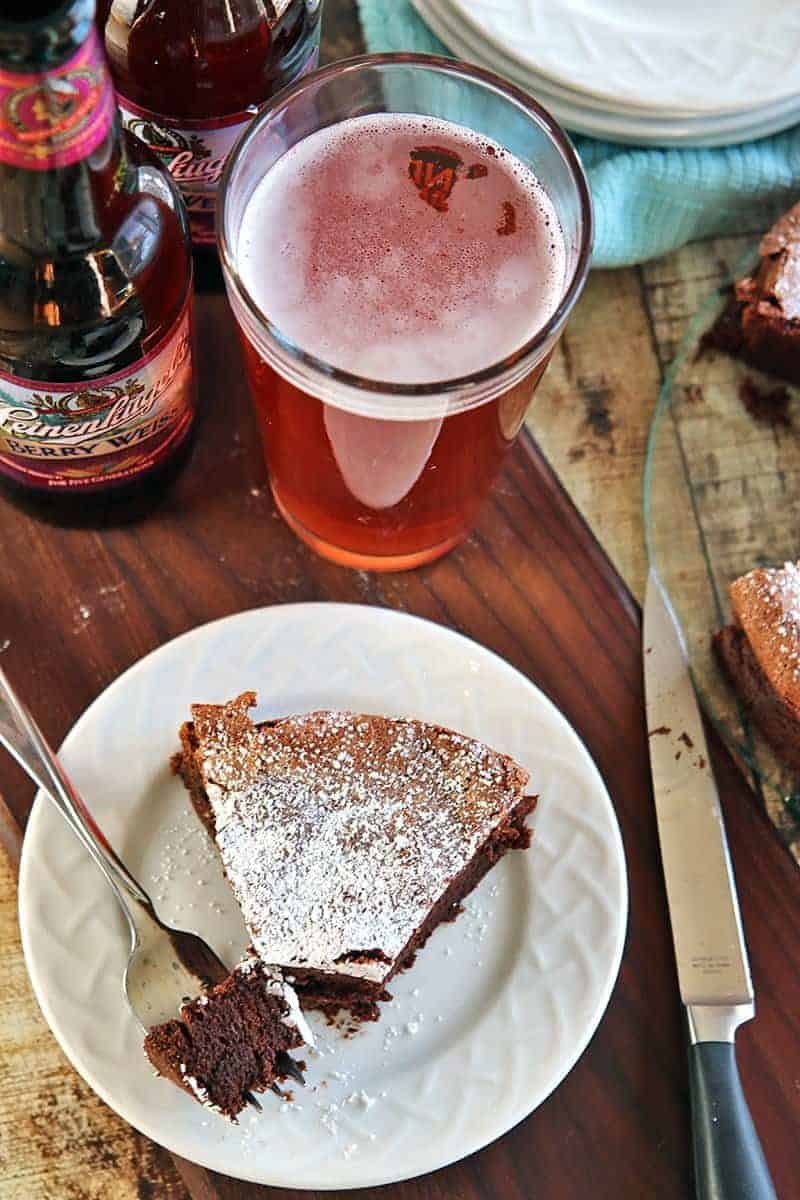 Flourless Chocolate Cake on a white plate with a glass of beer next to it