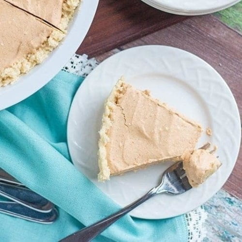 low carb pumpkin cheesecake recipe on a plate with a blue background with a fork with a bite of the cheesecake on it