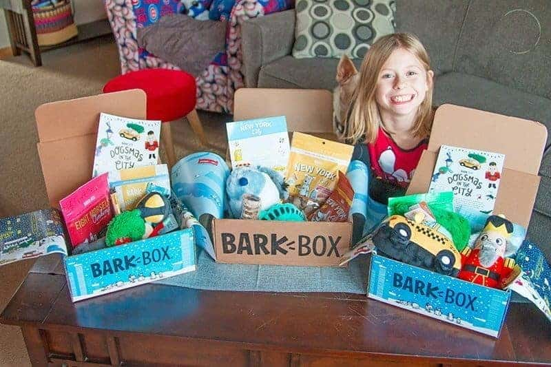 3 Barkboxes with a smiling girl