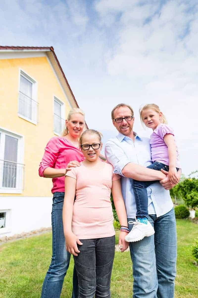 Family with a mom, dad and two daughters in front of a yellow house.