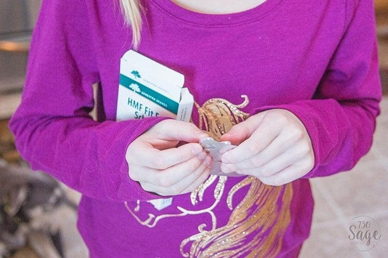 girl holding probiotics for kids