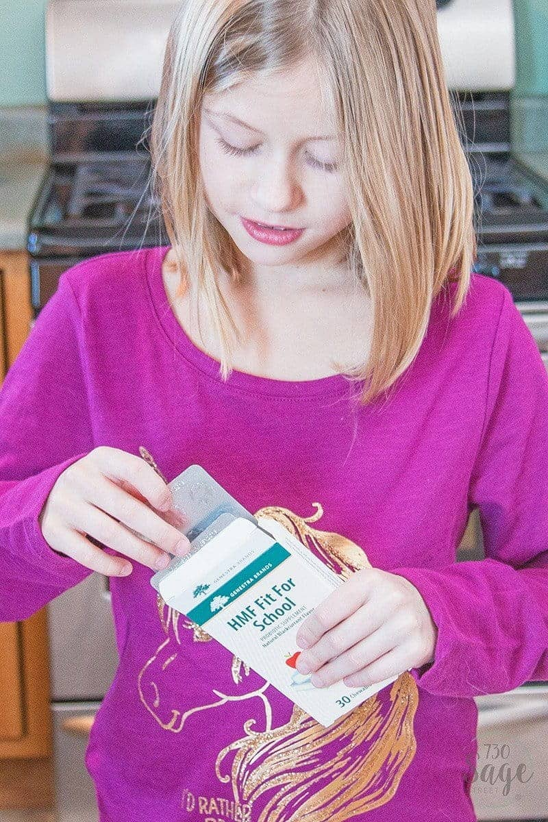 girl holding HMF Fit For School probiotics