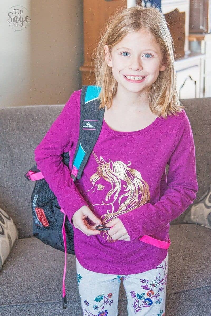 smiling girl with backpack in living room