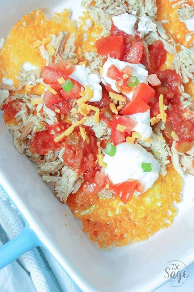 keto nachos - low carb nachos close up with sour cream in a blue casserole dish