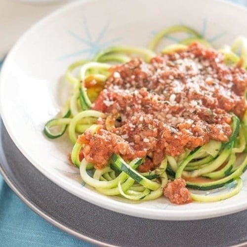 Side view of Low Carb Creamy Bolognese with Zucchini Noodles in a white bowl.