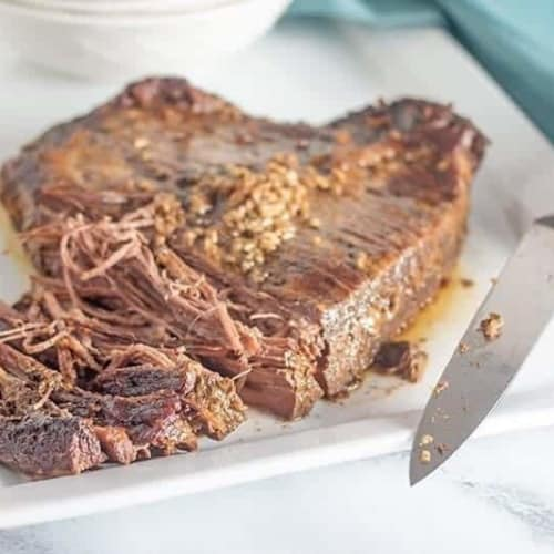 partially shredded beef brisket slow cooker on a white plate and a blue background with a knife