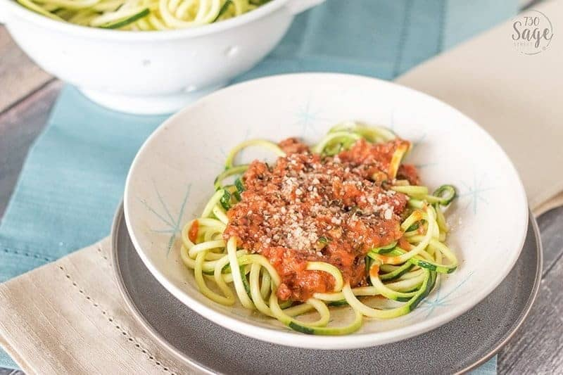 Low Carb Creamy Bolognese with Zucchini Noodles in a white bowl with a blue and tan background.