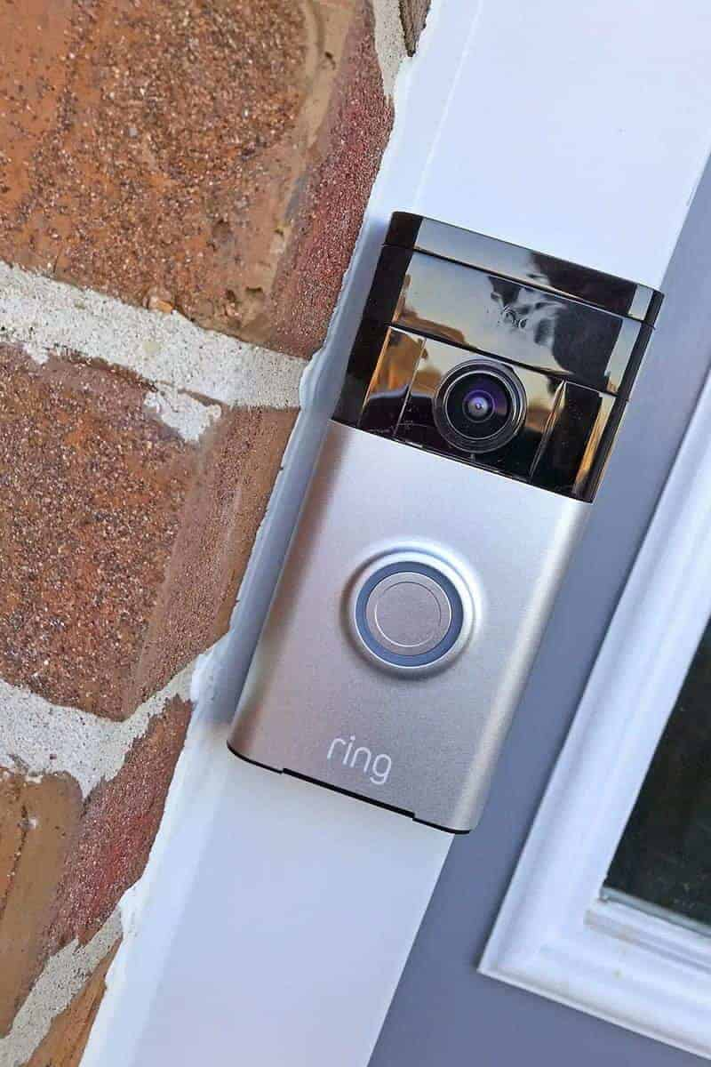 Ring Smart Doorbell on aluminum next to a brick wall.