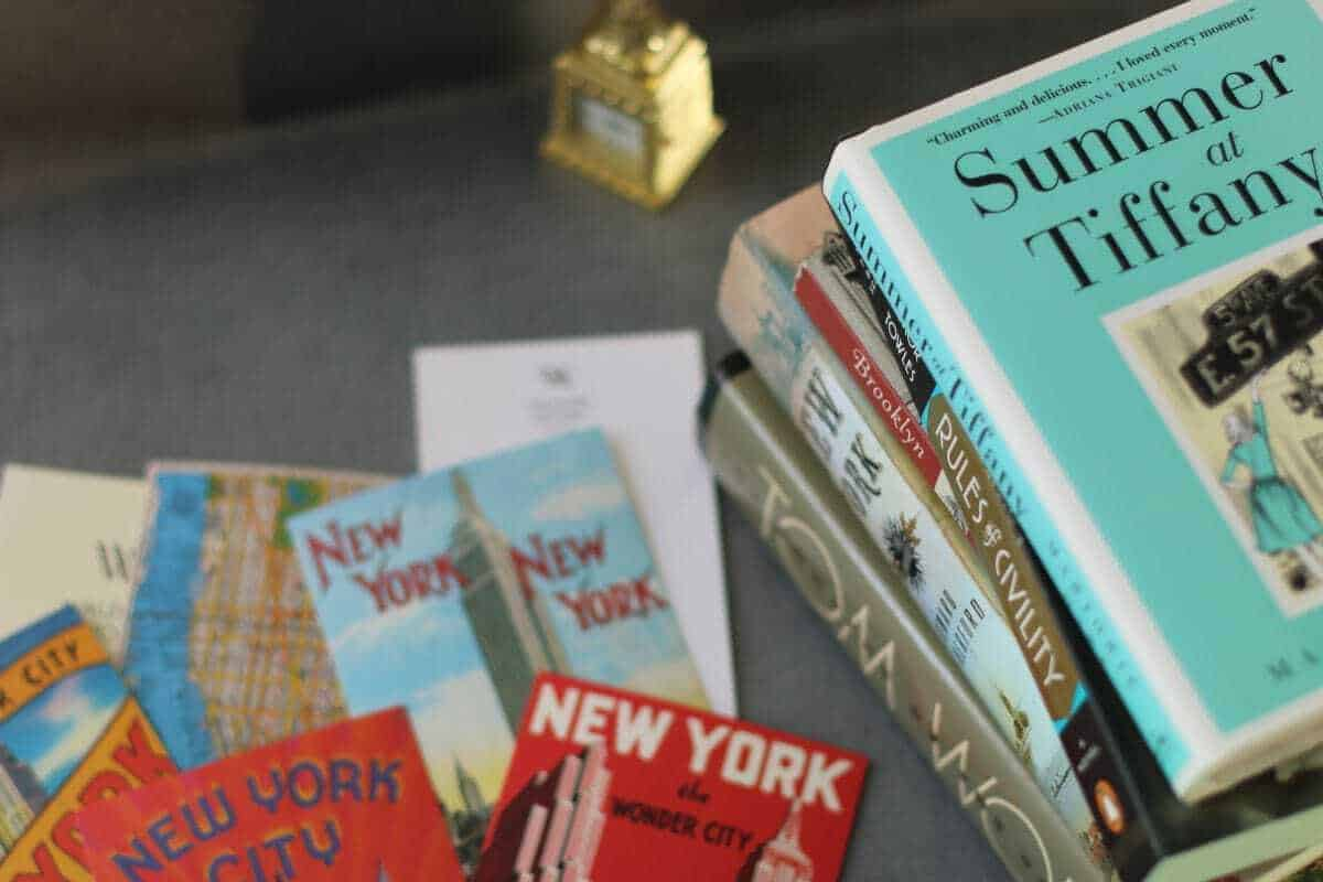 Stack of books and vintage postcards of New York City