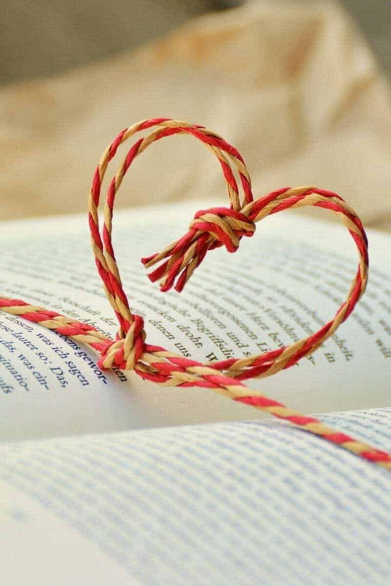 Red and cream twine heart on an open book