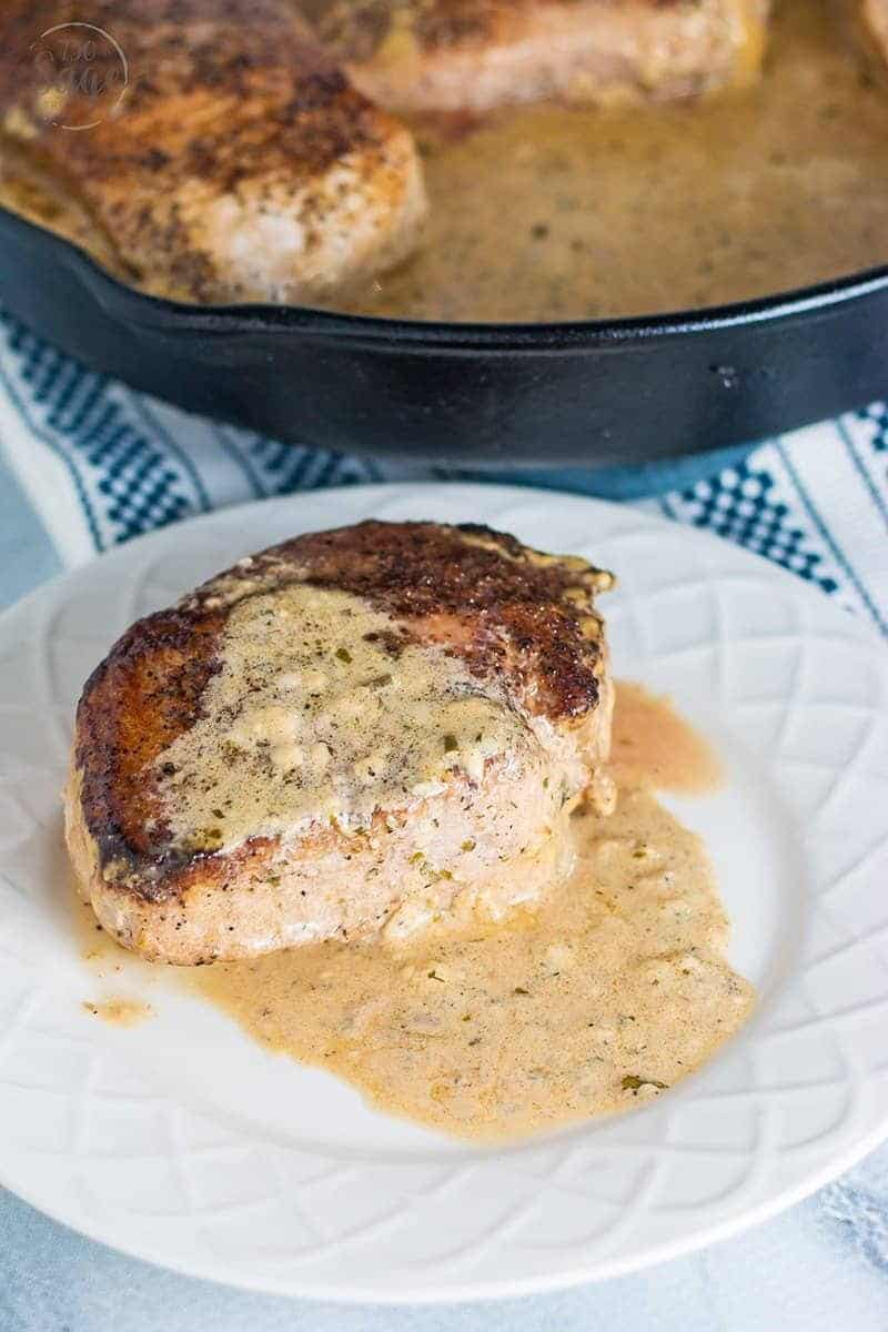 creamy ranch pork chops recipe on a white plate with blue patterned background and a cast iron pan in background
