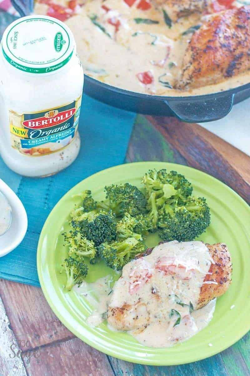 creamy Tuscan chicken on a green plate with a side of broccoli
