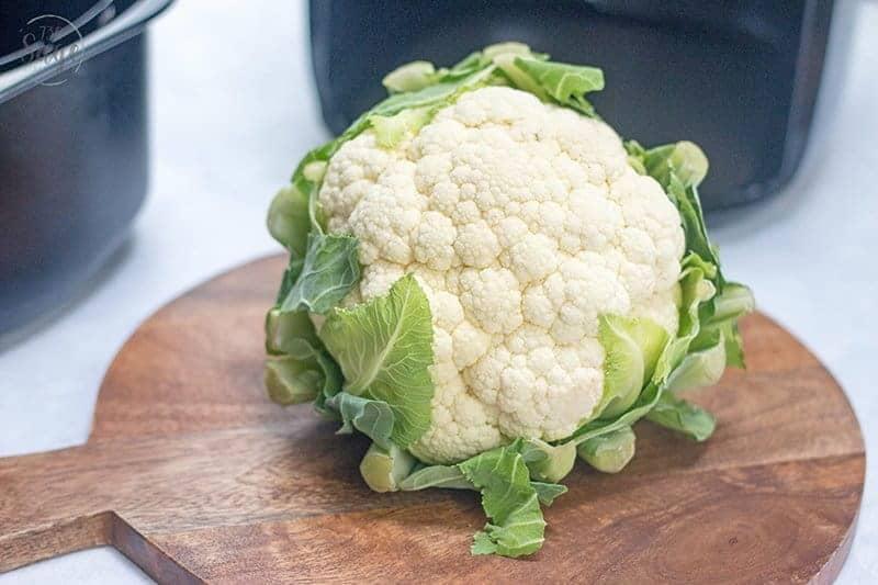head of cauliflower on a wood cutting board