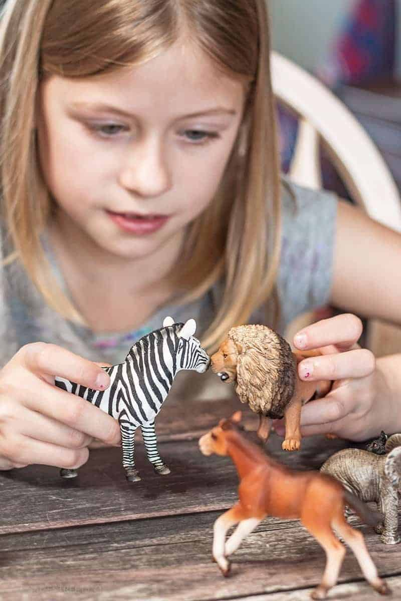 girl playing with Schleich toys zebra and lion