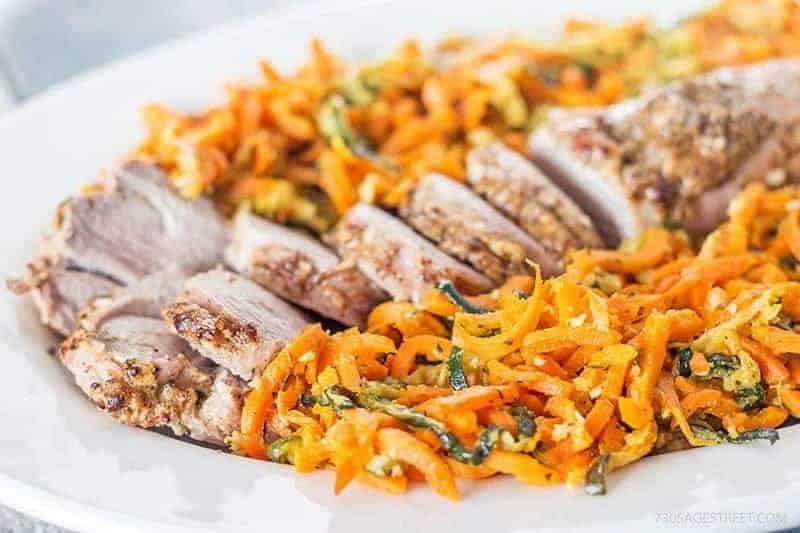vertical photo of pork tenderloin and colorful orange spiral carrots on a white plate