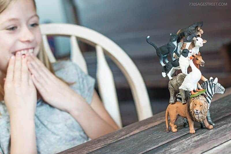girl playing with Schleich toys farm and wild animals