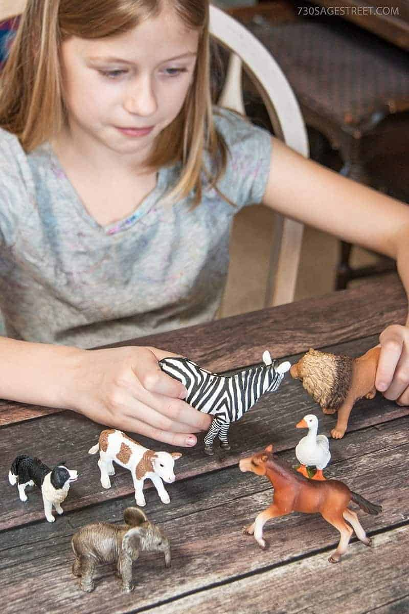 girl playing with Schleich toys wild animals