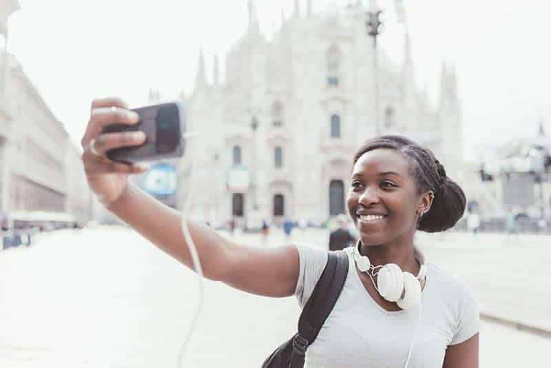 young woman taking a selfie in front of a church