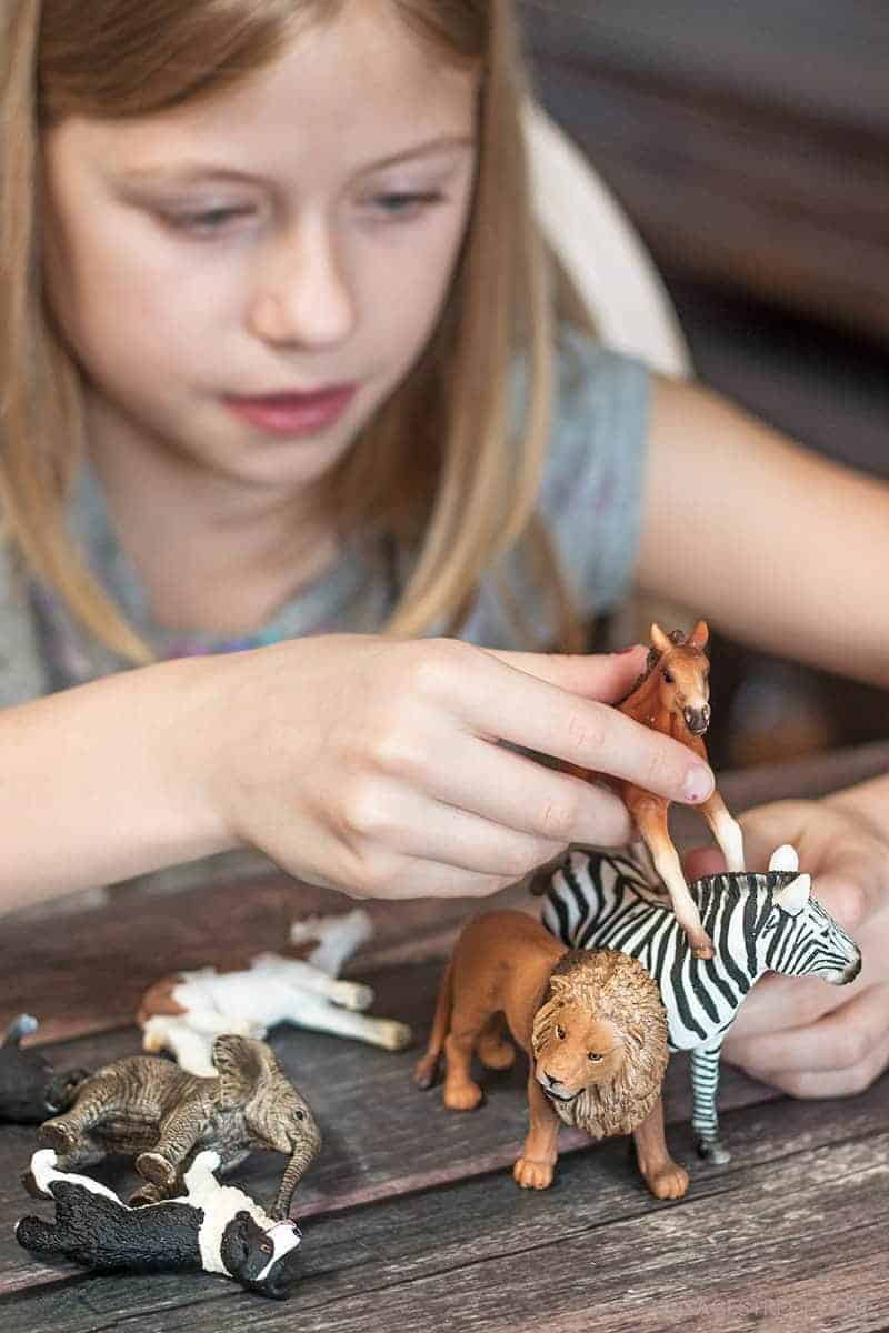 girl playing with Schleich toys farm animals