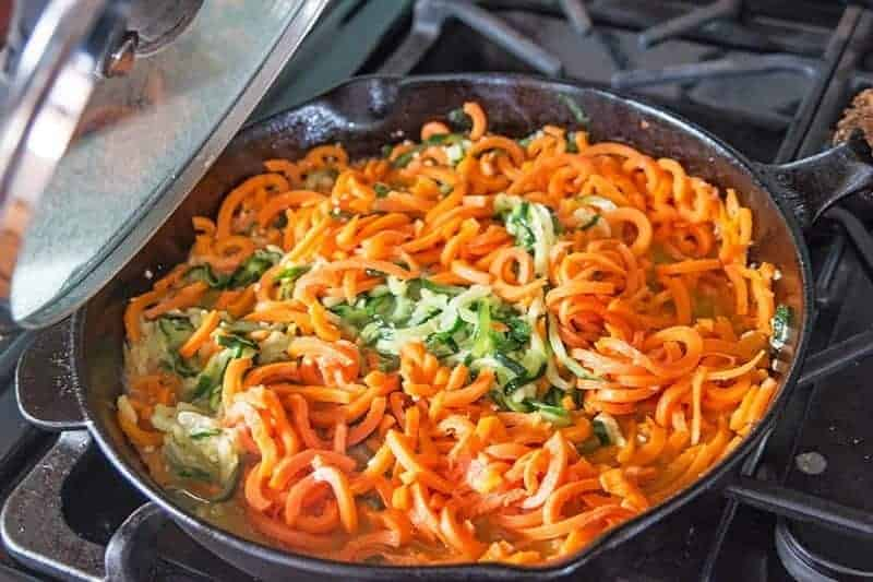 spiral carrots and zucchini saute in a cast iron pan