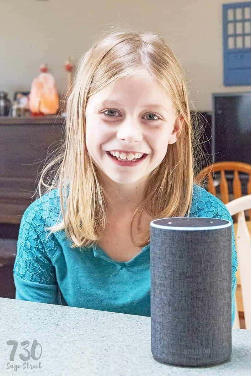 smiling girl in blue shirt with an Amazon Echo with Alexa Skill Blueprints