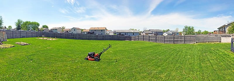 lawn mower in a panoramic photo with a fence in the background