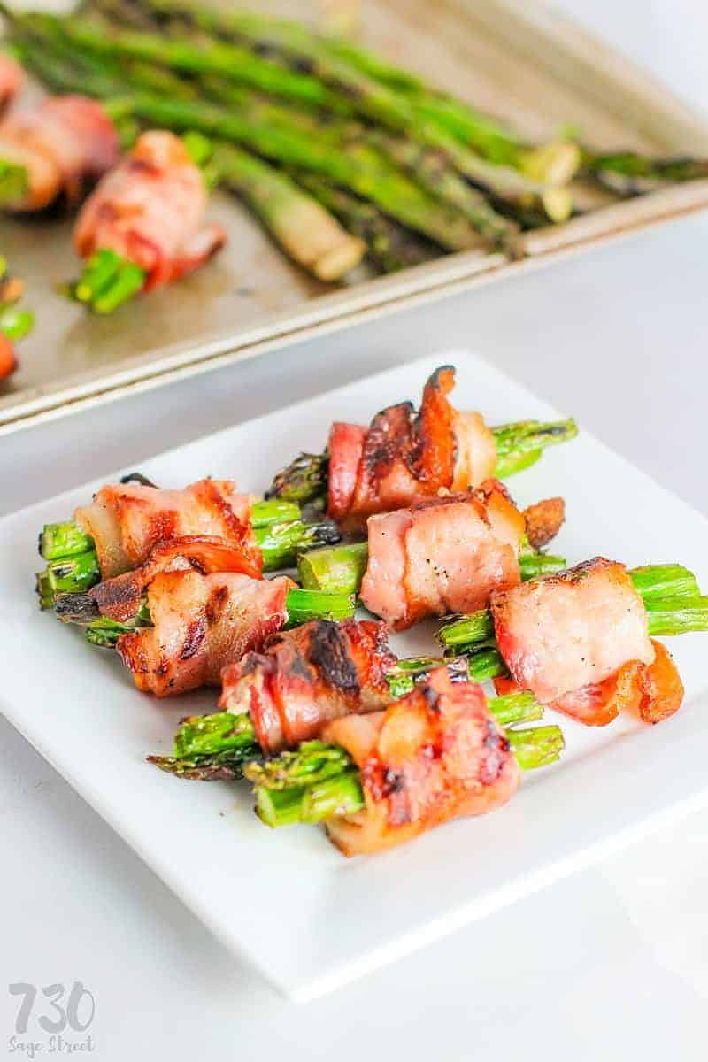 grilled bacon wrapped asparagus on a white plate