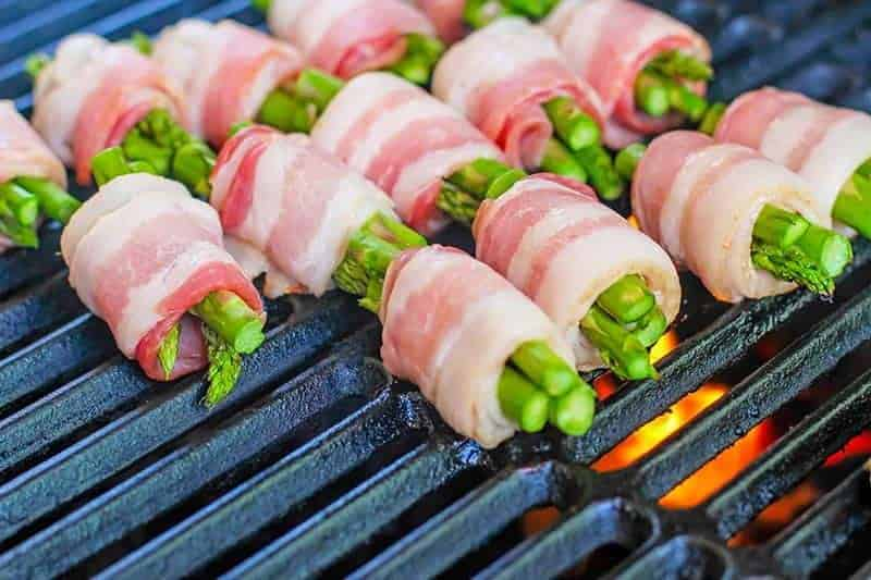 uncooked bacon wrapped asparagus on a grill