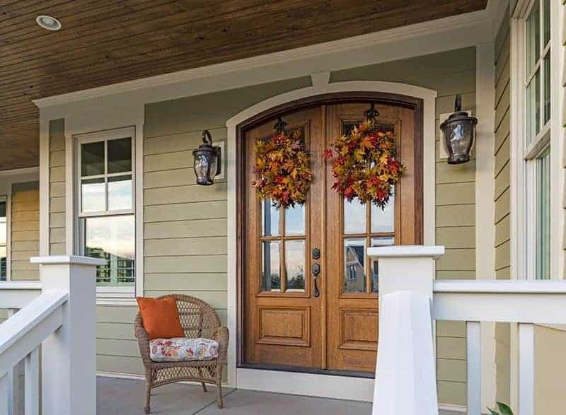 light green porch and wood doors with James Hardie siding