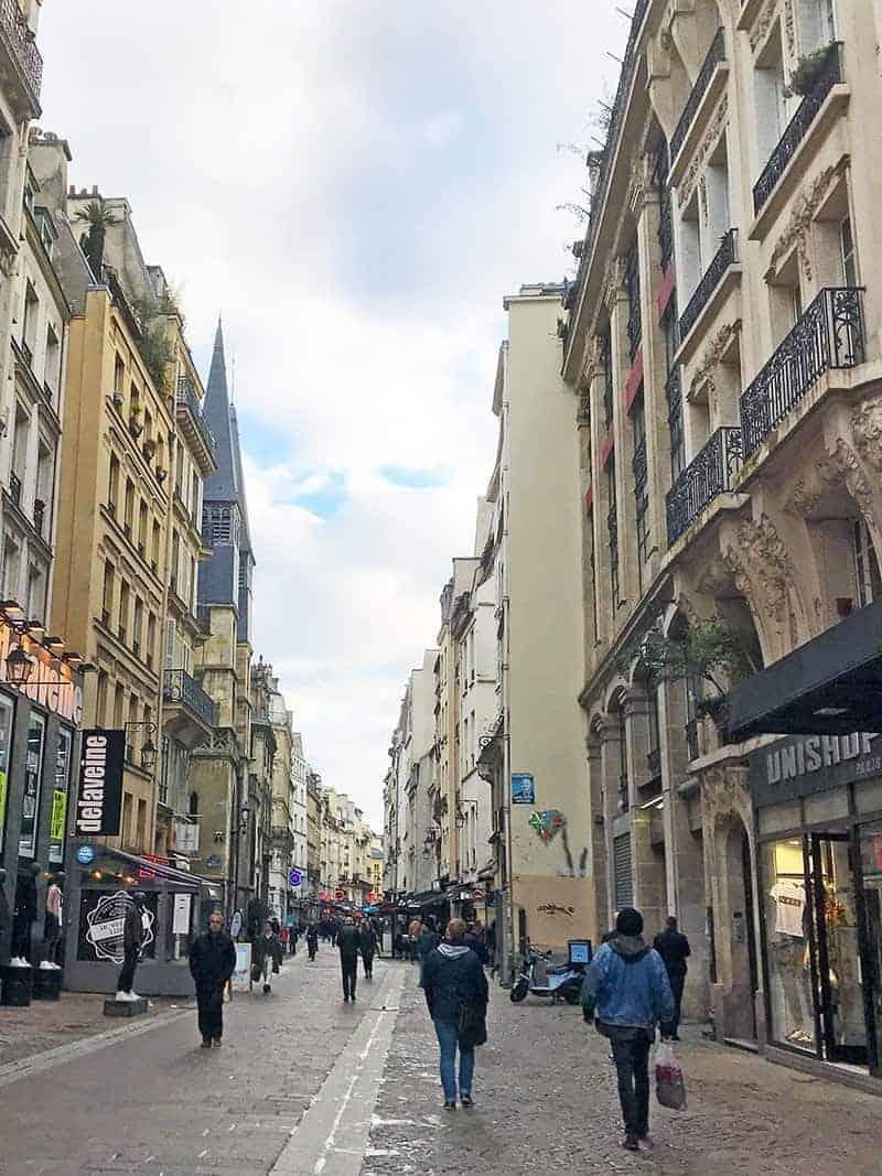 people walking in Paris down a typical street