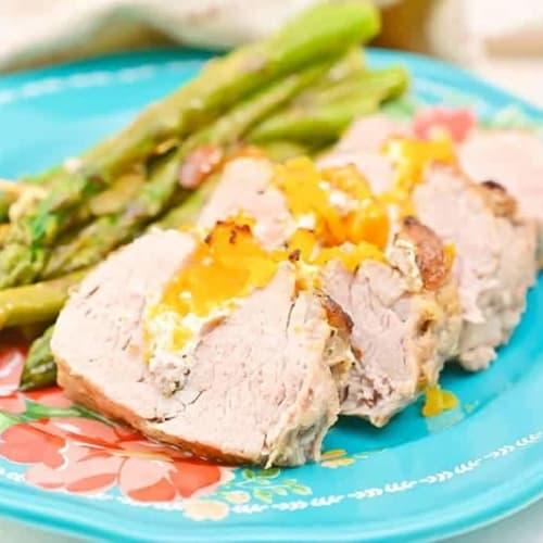 stuffed pork tenderloin on a blue plate with a side of asparagus