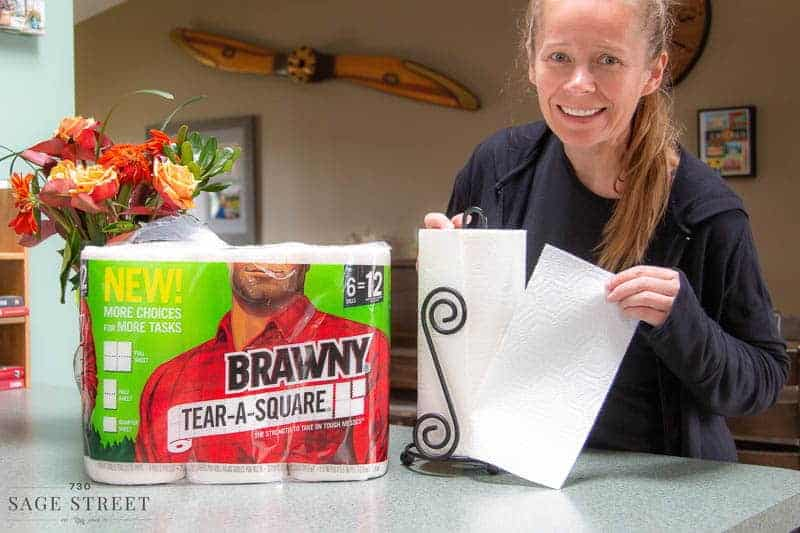 woman tearing a half sheet of paper towel off a roll of Brawny Tear-A-Square paper towels.