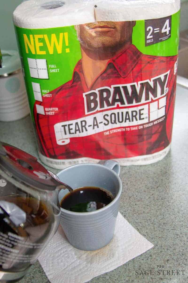 coffee pot pouring a cup of coffee with a package of Brawny paper towels in the background