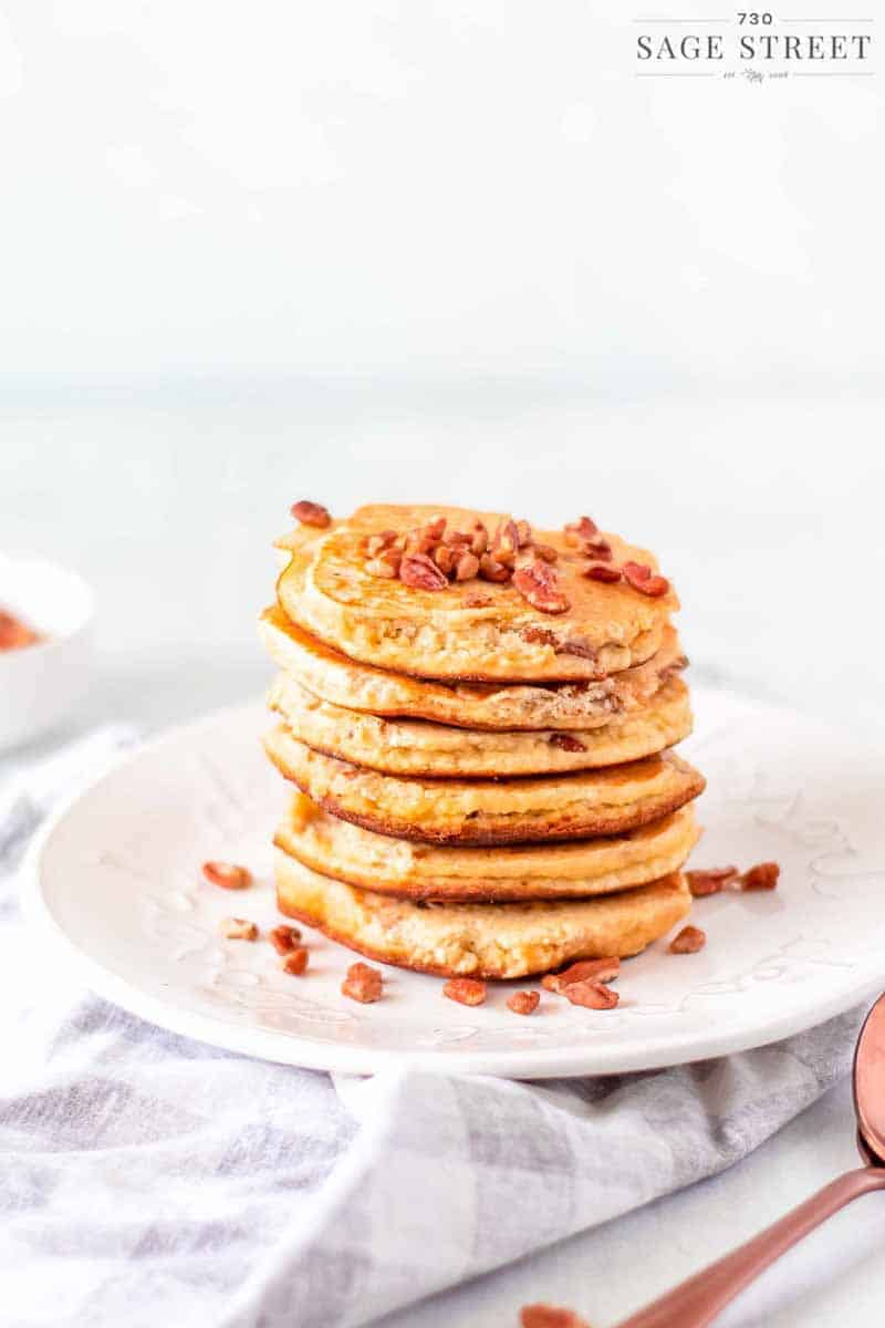 keto pancakes made with ricotta cheese on a white plate sprinkled with pecans view from the side
