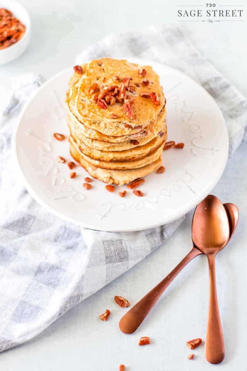 side view of keto pancakes made with ricotta cheese on a white plate sprinkled with pecans with copper spoons