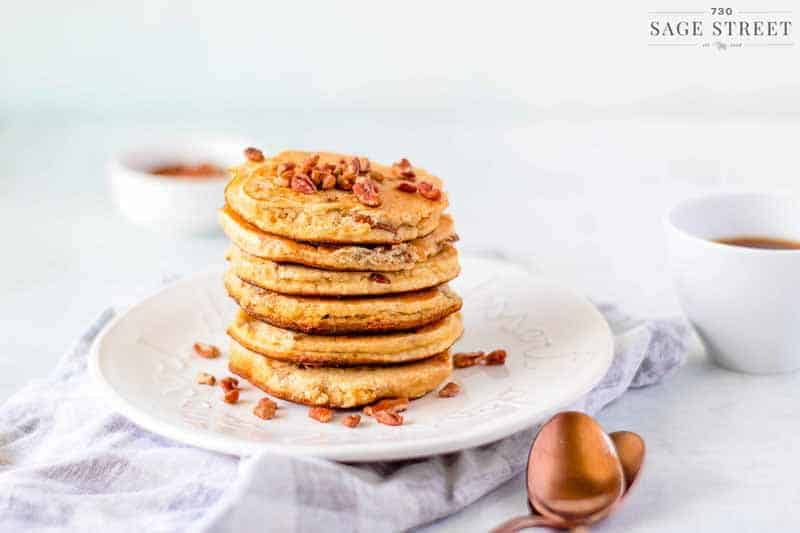 side view keto pancakes made with ricotta cheese on a white plate sprinkled with pecans