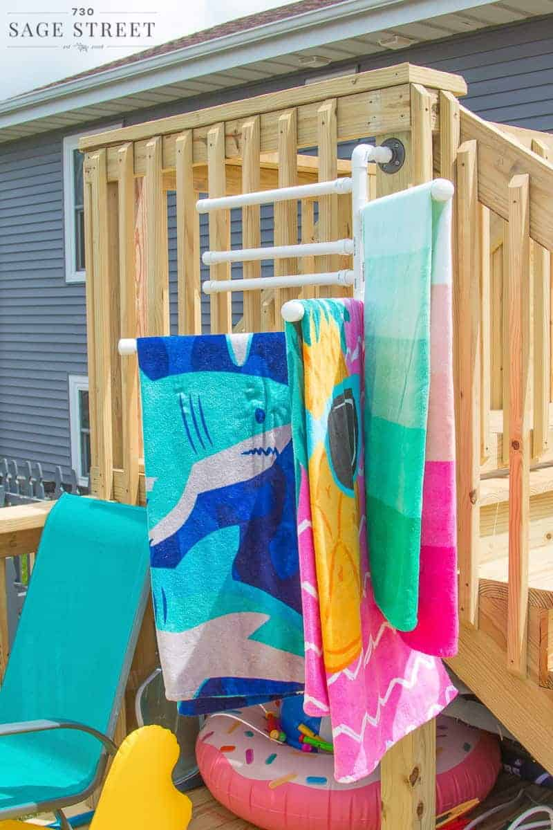 DIY pool towel rack hanging on a deck with colorful towels on it
