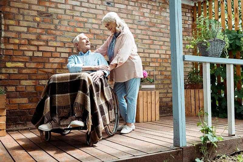 woman helping a man in a wheelchair