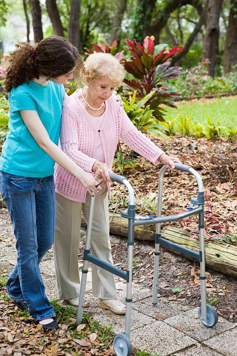 young woman helping an older woman with a walker