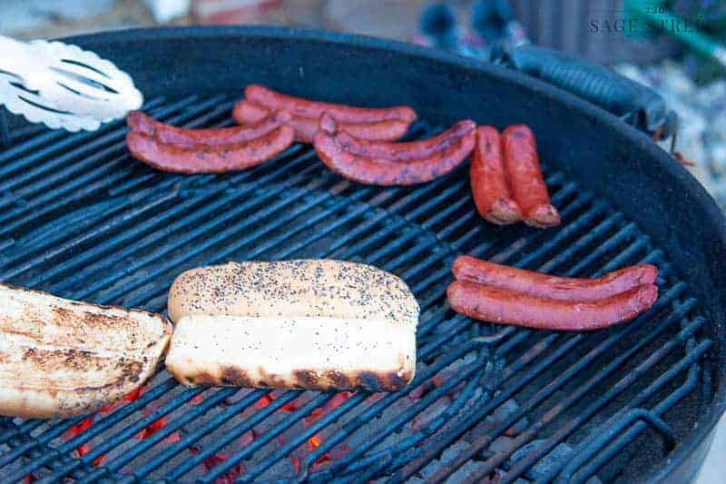 hot dogs and buns on the grill