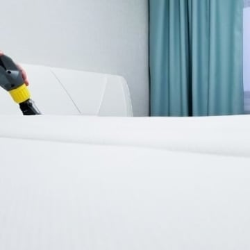 Woman cleaning a dirty mattress with a vacuum.