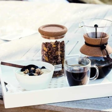 breakfast table with bowl of cereal, bodum pour over coffee with dark roast coffee, one cup of coffee full