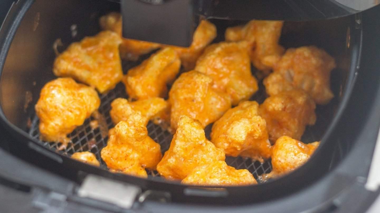 cooked cauliflower florets  in a airfryer basket